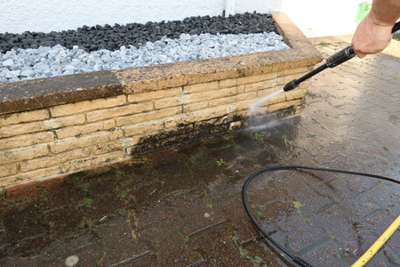 Photo pour man cleaning wall with high pressure cleaner in close up - image libre de droit