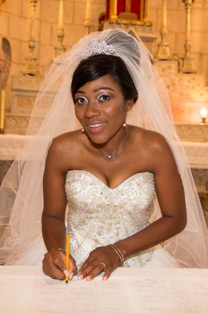 Foto de elegant african american black bride who signs the register during the wedding ceremony at the church - Imagen libre de derechos