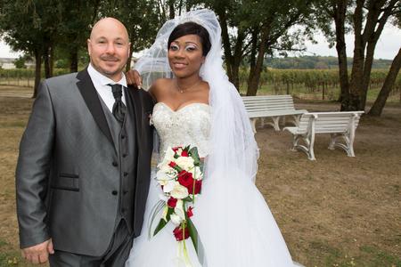 Foto de Amazing smiling mixed interracial wedding couple pretty black african bride and bald caucasian groom - Imagen libre de derechos