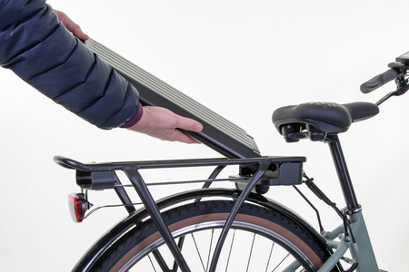 Photo pour man removes electric bike battery close up on white background - image libre de droit