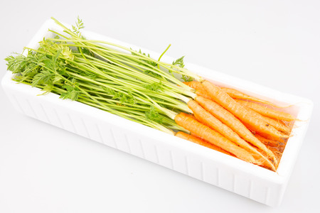 polystyrene white box industrial with fine small carrots for sale in white backgroundの写真素材