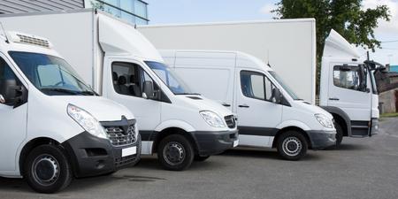 Photo pour white delivery service van trucks cars in front of factory warehouse - image libre de droit