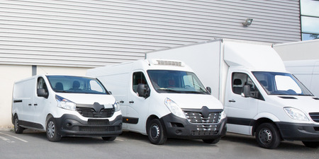 Photo for specialized delivery society parking with several white small trucks van - Royalty Free Image