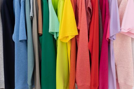 Photo pour Rainbow colors clothes on hangers for background - image libre de droit