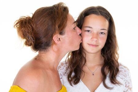 Foto de two caucasian lovely women adult mother kiss cheek her teenage daughter girl standing isolated over white background - Imagen libre de derechos