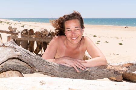 Photo pour Portrait of smiling brunette woman lying on driftwood beach - image libre de droit