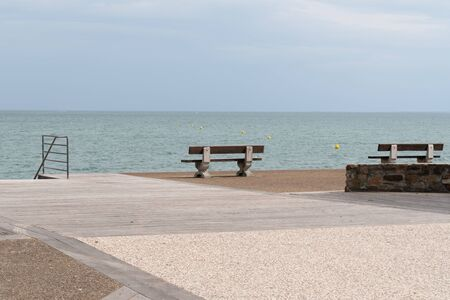Benches on the boardwalk square in front of atlantic beach in Saint Vincent sur jard in Vendée France