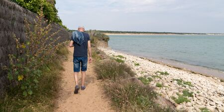 Retired senior man back walk seaside beach sand and rocks in Saint Vincent sur Jard in Vendée web banner template header France