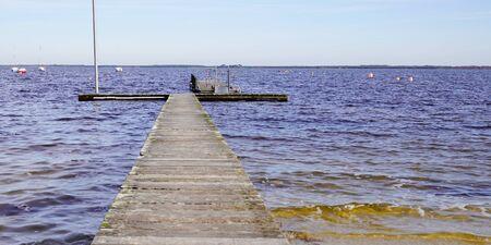 Photo pour wooden pier on the shore of a large lake of Maubuisson Carcans France - image libre de droit