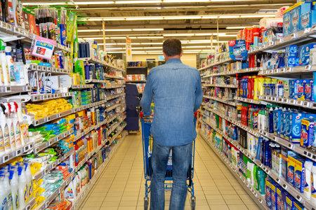 Photo pour Bordeaux , Aquitaine / France - 03 30 2020 : Back of man walking in supermarket with shopping cart - image libre de droit