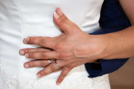 Photo pour Wedding rings and couple hands fingers bride and groom in love over marriage dress background - image libre de droit