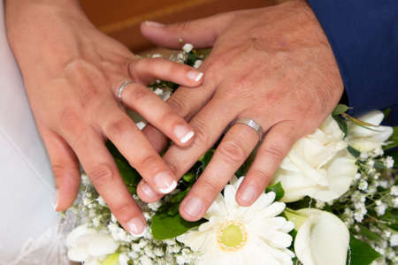 Photo pour groom man and bride woman fingers hands with wedding rings over marriage bouquet flowers - image libre de droit