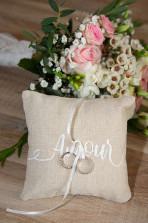 Photo pour two wedding rings on natural pillow with ribbon with amour text means love in french and flowers decoration - image libre de droit