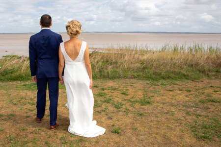 Photo pour Bride and groom on their wedding day outdoors aside river in back rear view with copy side - image libre de droit
