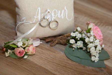 Photo pour two wedding rings on brown natural pillow with ribbon with write amour text means love in french and flowers decoration - image libre de droit