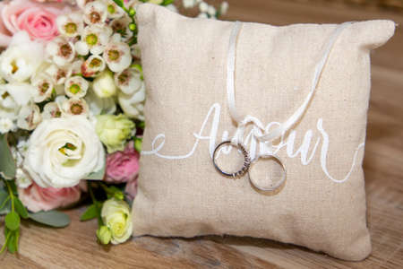 Photo pour two wedding rings on brown natural pillow with ribbon and amour love text and flowers bouquet - image libre de droit