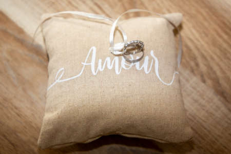 Photo pour wedding rings on small natural brown pillow with ribbon and amour text means love in french on wooden table background - image libre de droit
