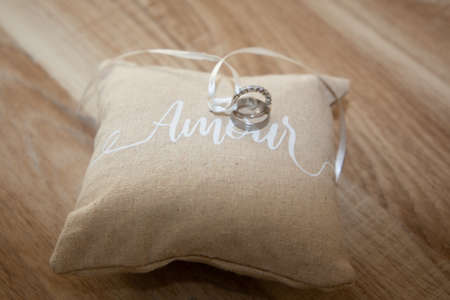 Photo pour wedding rings on small cushion natural brown pillow with ribbon and amour text means love in french on wooden table background - image libre de droit