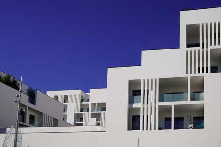 Photo pour New modern facade white apartment building exterior architecture in blue summer sky - image libre de droit