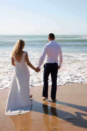 Photo pour wedding couple back rear view in love on sea beach bride and groom in marriage day on sand ocean coast - image libre de droit