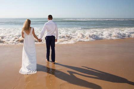 Photo pour back view wedding couple walking on romantic sand sea beach - image libre de droit