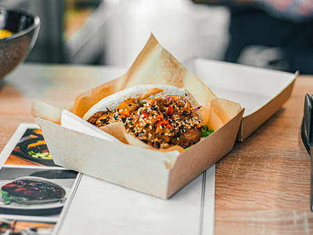 Photo pour Bao with chicken in paper in carton box. Rice buns with meat, vegetables filling with sauce, sprinkled with sesame seeds. Fast food in a cafe, restaurant - image libre de droit
