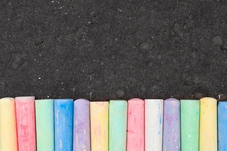 Photo for Colorful pastel sidewalk chalk on dark asphalt background. Top view - Royalty Free Image