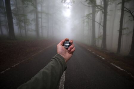 Photo for Survior young adult hiker searching the direction to home with navigational compass in the foggy forest. - Royalty Free Image