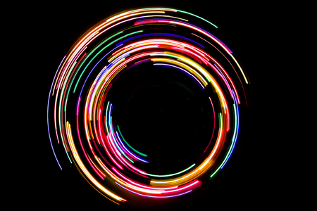 Abstract rotating neon lights texture with black space.