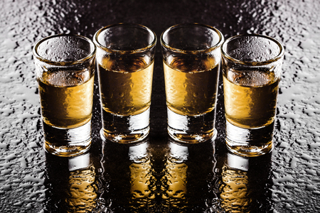 Photo pour Orange, yellow vodka glass shots in a row on wet black surface. Weekend party drinking background. - image libre de droit