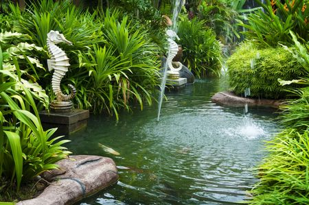 Tropical zen garden view with fountain and green plants.