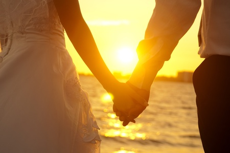 Foto de Young adult male groom and female bride holding hands on beach at sunset. - Imagen libre de derechos