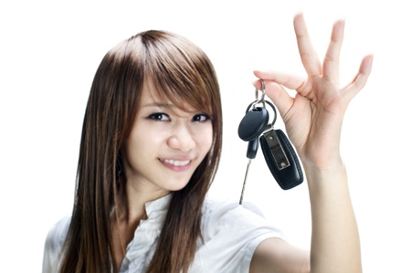 Young girl holding car key on white background