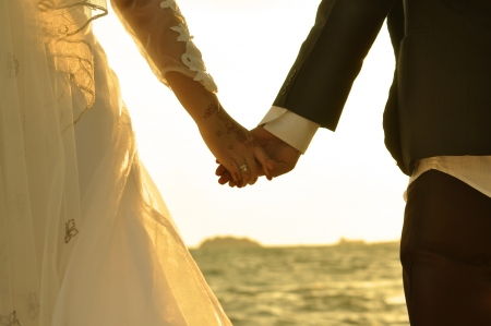 Young adult male groom and female bride holding hands on beach at sunset.