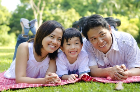 Outdoor happy Asian family lying on floor