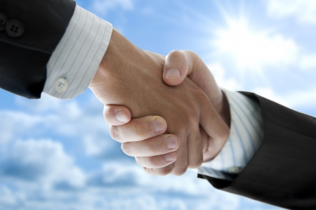 Businessmen shaking hands over blue sky, low angle view.