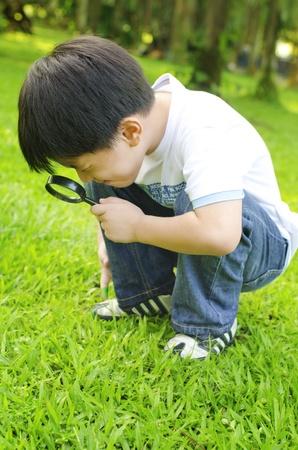 Little boy exploring nature by magnifier