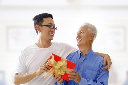 Happy Mixed race Asian father receiving present from his son