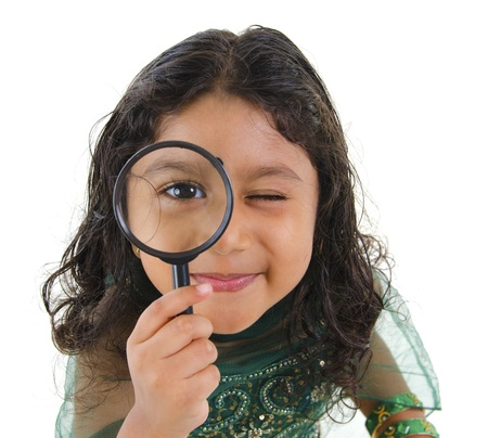A little Indian girl peers at the camera through a magnifying glass, isolated on white background