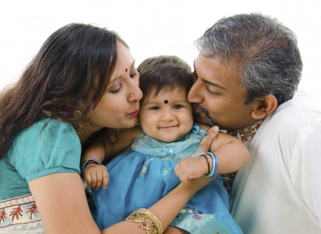Photo for Indian parents giving their daughter a kiss, isolated on white background - Royalty Free Image