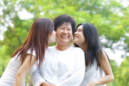 Photo pour Young Asian daughter kissing their senior mother, outdoor park - image libre de droit