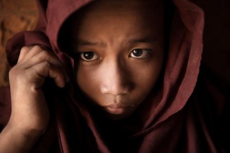 Photo pour A young novice monk covered his head by robe - image libre de droit