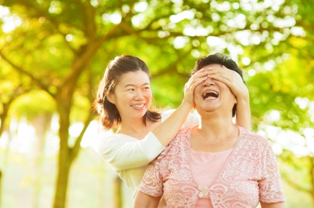 Photo pour Asian adult daughter covering her senior mother eyes by hands at outdoor park - image libre de droit