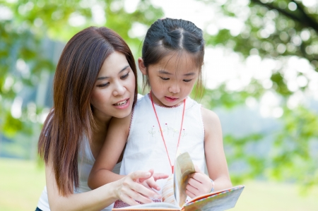 Beautiful little girl reading book with her mother and smiling. Summer park in background.
