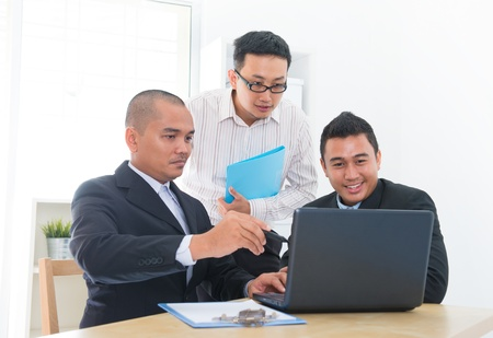 Southeast Asian business team discuss in office