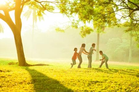 Foto de Asian family outdoor quality time enjoyment, asian people playing during beautiful sunrise - Imagen libre de derechos