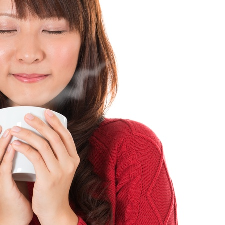 Photo pour Beautiful mixed Asian young woman enjoying a cup of coffee, with coffee smoke and copy space on right, isolated on white background. - image libre de droit