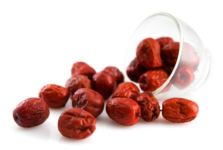 Dried red date spill from a glass. Chinese jujube. Traditional herbal medicine isolated on white background.