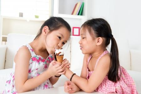 Photo pour Asian girls sharing an ice cream - image libre de droit