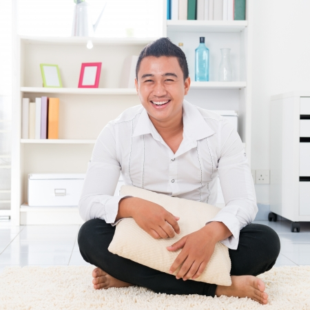 Young Asian man smiling happy. Lifestyle Southeast Asian man at home. Handsome Asian male model.